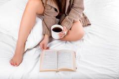 Femme attirante avec une tasse de café et de livre sur le lit Photo libre de droits