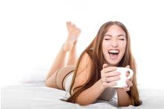 Femme attirante avec une tasse de café sur le lit Rire de l'oreille à l'oreille Photo libre de droits