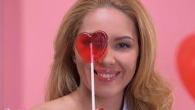 Femme attirante ayant l'amusement avec la lucette en forme de coeur, flirtant à la caméra banque de vidéos