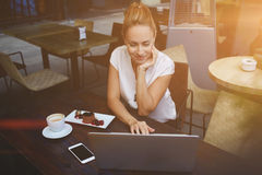 Femme attirante causant dans le réseau par l'intermédiaire du filet-livre portatif pendant le petit déjeuner de matin dans le caf image stock