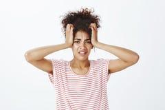 Femme attirante contrariée intense dans le T-shirt rayé, tenant des mains sur la tête comme si la serrant, fronçant les sourcils  photos libres de droits