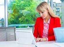 Femme attirante d'affaires dans le bureau avec l'ordinateur portable photographie stock