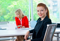 Femme attirante d'affaires dans le bureau avec le collègue à l'arrière-plan Image libre de droits