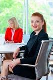 Femme attirante d'affaires dans le bureau avec le collègue à l'arrière-plan Images libres de droits
