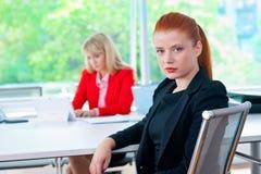 Femme attirante d'affaires dans le bureau avec le collègue à l'arrière-plan Photos libres de droits