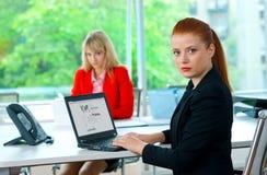 Femme attirante d'affaires dans le bureau avec le collègue à l'arrière-plan photographie stock