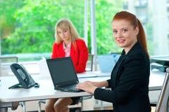 Femme attirante d'affaires dans le bureau avec le collègue à l'arrière-plan Photo libre de droits