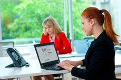 Femme attirante d'affaires dans le bureau avec le collègue à l'arrière-plan Photo stock