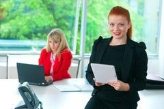 Femme attirante d'affaires dans le bureau avec le comprimé Photos stock