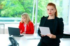Femme attirante d'affaires dans le bureau avec le comprimé Image libre de droits