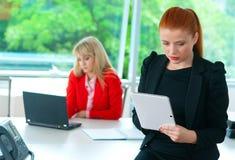 Femme attirante d'affaires dans le bureau avec le comprimé Photo libre de droits