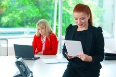 Femme attirante d'affaires dans le bureau avec le comprimé images libres de droits