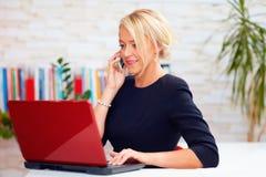 Femme attirante d'affaires parlant au téléphone dans le bureau Photo libre de droits