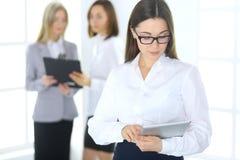 Femme attirante d'affaires travaillant avec un PC de comprimé dans la perspective des collègues Avocat ou spécialiste en secrétai photos libres de droits