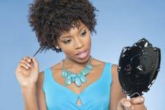 Femme attirante d'Afro-américain regardant elle-même dans le miroir au-dessus du fond coloré Photographie stock libre de droits