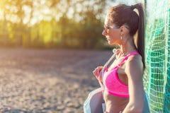 Femme attirante d'ajustement dans les vêtements de sport s'exerçant dehors, athlète féminin avec le corps parfait se reposant apr Photos stock