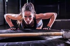 Femme attirante d'ajustement posant sur le pneu avec le marteau de forgeron dans le gymnase de forme physique photos stock