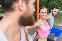 Femme attirante d'ajustement souriant pendant l'étirage de la routine tandis qu'exe Photographie stock libre de droits