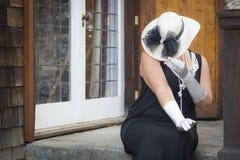 Femme attirante dans l'équipement d'années '20 sur le porche de l' Image libre de droits