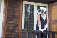 Femme attirante dans l'équipement d'années '20 sur le porche de l' Images libres de droits