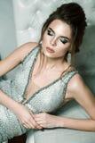 Femme attirante dans la robe de soirée brillante argentée, coiffure et ho image stock