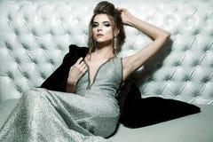 Femme attirante dans la robe de soirée brillante argentée, coiffure et ho photo stock