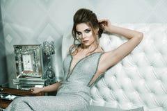 Femme attirante dans la robe de soirée brillante argentée, la coiffure et le h photo stock