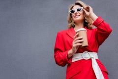 femme attirante dans la veste rouge tenant le café dans la tasse de papier et touchant des lunettes de soleil photo libre de droits