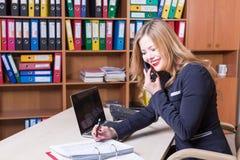 Femme attirante dans le bureau parlant sur le téléphone et le sourire Photographie stock libre de droits
