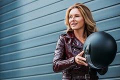 femme attirante dans le casque de moto de participation de veste en cuir sur la rue photo stock