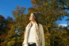 Femme attirante dans le chandail et le chapeau appréciant le soleil un jour de calme d'automne Image stock