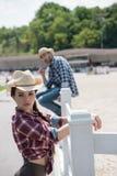 Femme attirante dans le chapeau de cowboy ne se penchant aucune barrière et regardant loin Photo stock