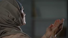 Femme attirante dans le hijab priant soulevant des mains, thanksgiving islamique de culture banque de vidéos