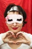 Femme attirante dans le masque de sommeil faisant la forme de coeur avec ses mains Photos stock