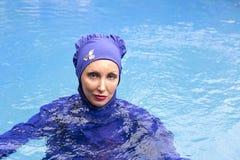 Femme attirante dans un burkini musulman de vêtements de bain en mer photographie stock