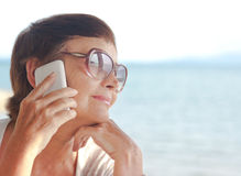 Femme attirante de 50 ans avec un téléphone portable Photographie stock