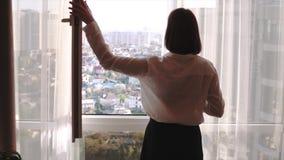 Femme attirante de brune appréciant son café aromatique et regardant dans la fenêtre du haut plancher sur les cottages égalisants banque de vidéos