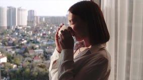 Femme attirante de brune appréciant son café aromatique et regardant dans la fenêtre du haut plancher sur les cottages égalisants clips vidéos