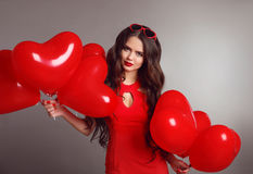 Femme attirante de brune de portrait d'amour en rouge avec le balloo de coeur Photos stock