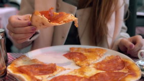 Femme attirante de brune tenant la tranche de pizza et la mordant La fille affamée dînent dans le restaurant d'aliments de prépar Images stock