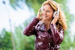 femme attirante de sourire dans la musique de écoute de veste en cuir photos libres de droits