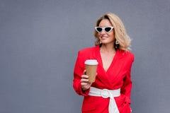 femme attirante de sourire dans la veste rouge tenant la tasse de café jetable photos stock