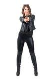 Femme attirante de sourire heureuse dans l'arme à feu de pointage en cuir noire à l'appareil-photo Image stock