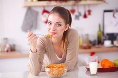 Femme attirante de sourire prenant le petit déjeuner dans l'intérieur de cuisine Femme attirante de sourire Image libre de droits