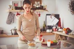 Femme attirante de sourire prenant le petit déjeuner dans l'intérieur de cuisine Femme attirante de sourire photographie stock libre de droits