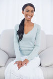 Femme attirante de sourire s'asseyant sur le sofa confortable Image stock