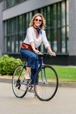 femme attirante de sourire s'asseyant sur le vélo photo stock
