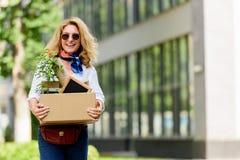 femme attirante de sourire tenant la boîte de papier avec la substance de bureau image libre de droits