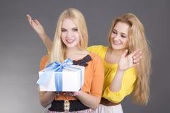 Femme attirante donnant un présent à son ami étonné Images stock