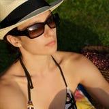 Femme attirante et jeune avec le chapeau du soleil s'exposant au soleil Photo stock